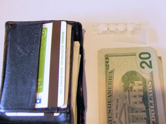 Four aspirin wrapped in scotch tape beside my wallet.