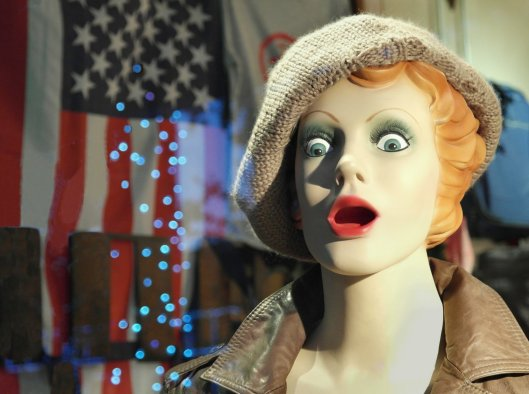 An American flag sheds stars to the astonishment of a mannequin.