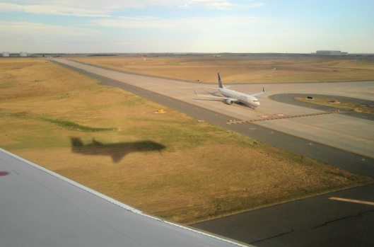 Airplane shadow landing in Denver International Airport.