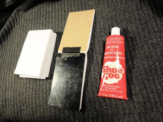 Cut a 3x5 plastic card and duct tape it along the glued edge