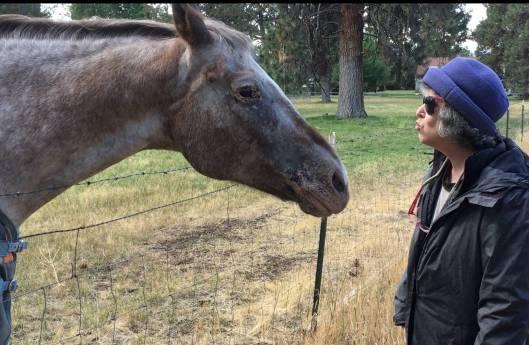 A woman throws a kiss to a horse.